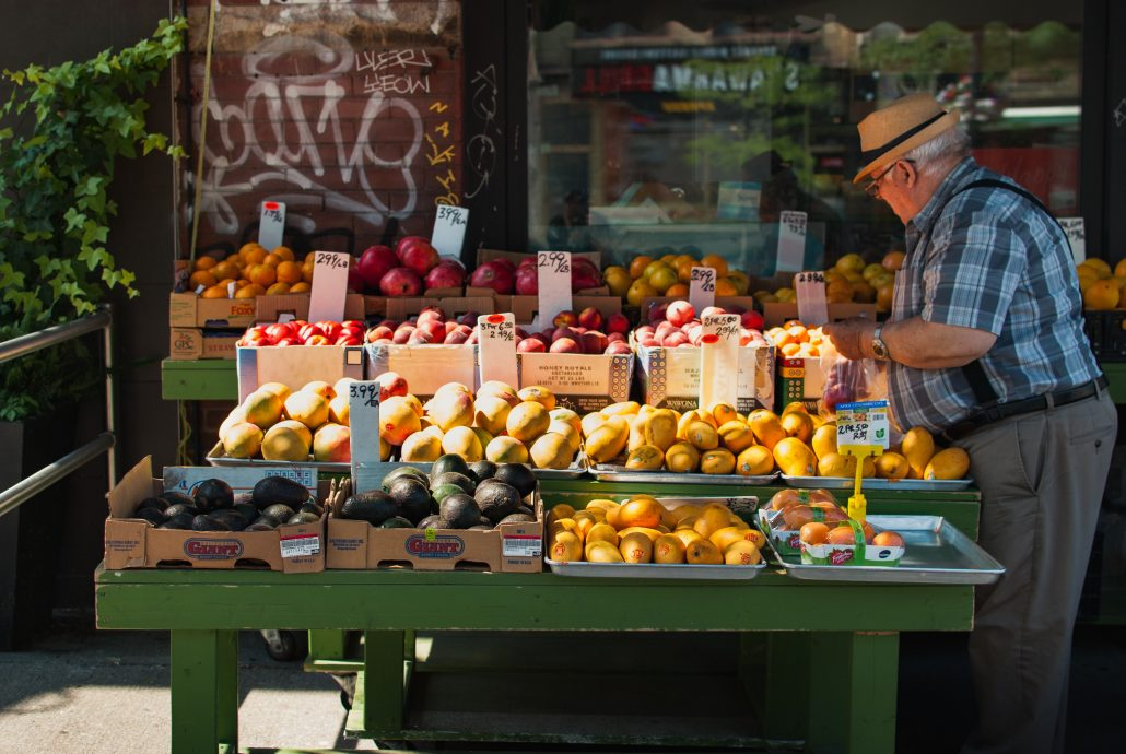 Man with fresh fruit and vegetable stand on a street
